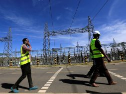 FILE PHOTO: Kenya Electricity Generating Company workers walk past the pylons of high-tension electricity power lines at the Olkaria II Geothermal power plant near the Rift Valley town of Naivasha