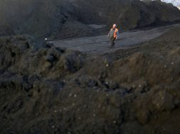 FILE PHOTO: Worker walks past coal piles at a coal coking plant in Yuncheng