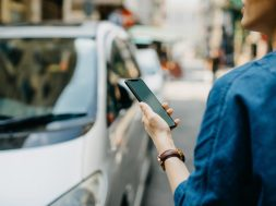 Woman ordering a taxi ride with mobile app on smartphone in the city