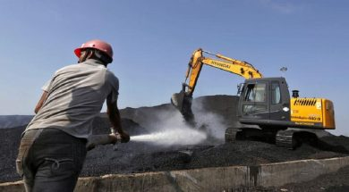 A worker sprays water over piles of coal as a bulldozer shifts coal at Mundra Port Coal Terminal in the western Indian state of Gujarat