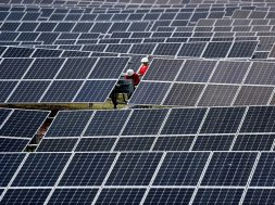 Workers inspect solar panels at a photovoltaic power station on a hill in Linyi
