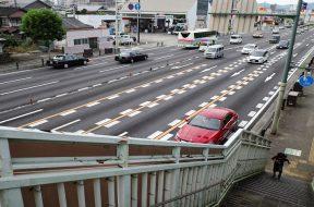 A schoolboy walks up the overhead bridge along a traffic junction in Beppu