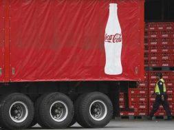 Security personnel walks near a truck at PT Coca-Cola Amatil Indonesia's factory in Cibitung