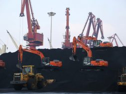 FILE PHOTO: Workers operate loaders unloading imported coal at a port in Lianyungang, Jiangsu